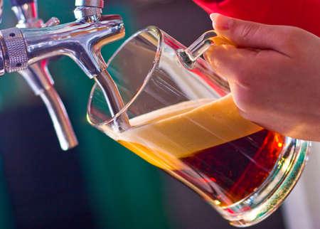 vidrio que se llena de cerveza de barril por el barman,