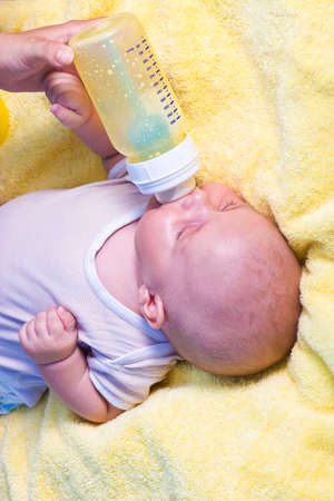 Mother give drink her son by feeding bottle photo