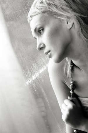 sad, beautiful young woman pining at the window Stock Photo