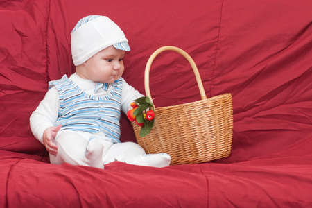 Funny little boy looking into the basket in the studio photo
