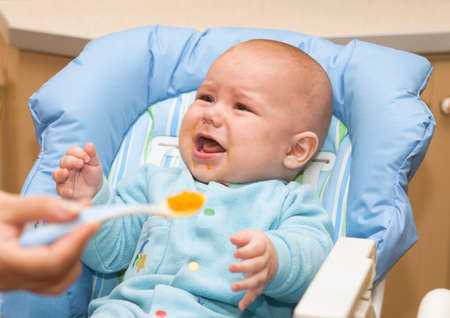 Portrait of cute baby boy while mother feeding Stock Photo - 16795039