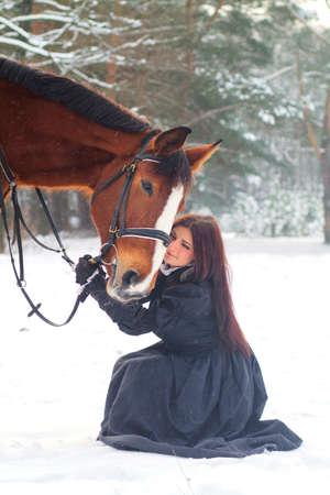 Mujer hermosa en vestido elegante y un caballo en invierno
