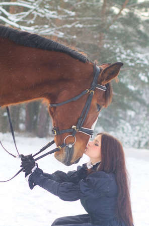 Beautiful woman in elegant dress and a horse in winter photo