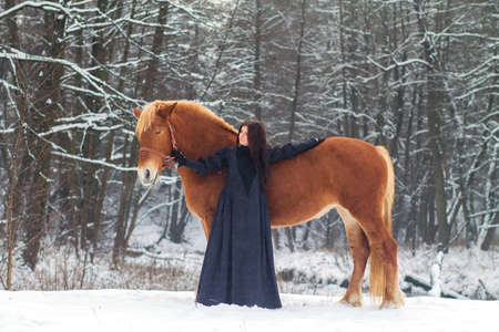 Beautiful woman in elegant dress and a horse in winter