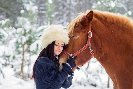 Beautiful woman in a fur hat and a horse in winter