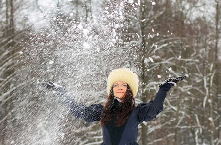 young woman playing with snow  in elegant dress and a fur hat