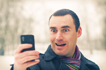 Man expresses emotion when talking on a cell mobile phone Stock Photo