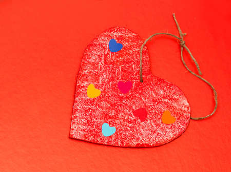 multicolored paper hearths on a wooden red heart  on red paper photo