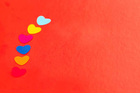 line of multicolored paper hearths on red paper Stock Photo - 17024606