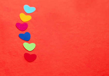 line of multicolored paper hearths on red paper Stock Photo - 17024545