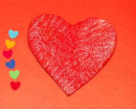 multicolored paper hearths with a wooden red heart  on red paper photo