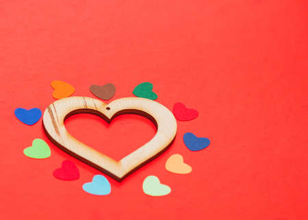 multicolored paper hearths around a wooden  heart  on red paper Stock Photo - 17024489