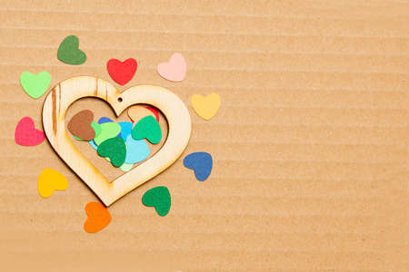 multicolored paper hearths with a wooden  heart  on grey cardboard with lines for text