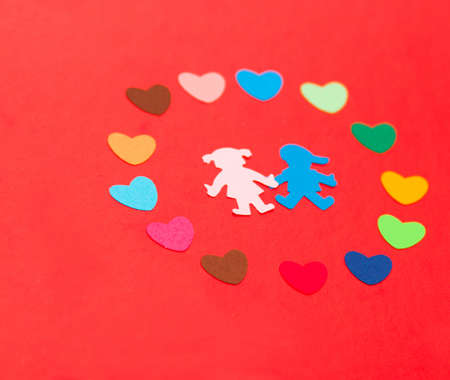 multicolored paper hearths around multicolored paper boy and girl on red paper photo
