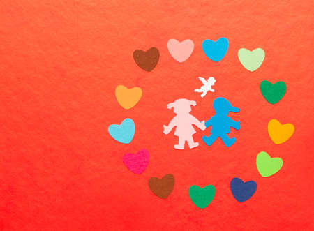 multicolored paper hearths around multicolored paper boy and girl with angel on red paper photo