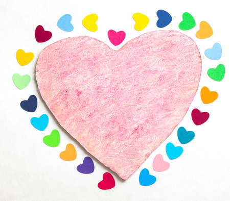 multicolored paper hearths on a wooden pink heart  on white paper