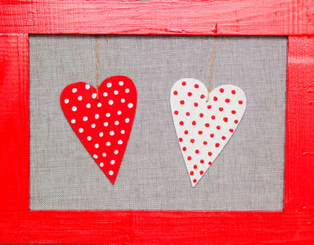 two wooden multicolored hearts in the red frame on grey background Stock Photo - 17174507