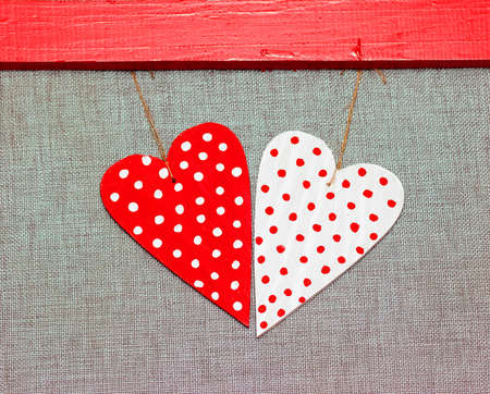two wooden multicolored hearts in the red frame on grey background Stock Photo - 17174509