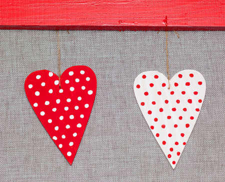 two wooden multicolored hearts in the red frame on grey background Stock Photo - 17174515