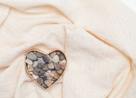 stone heart in cardboard box in the form of heart on linen fabric Stock Photo - 17174498
