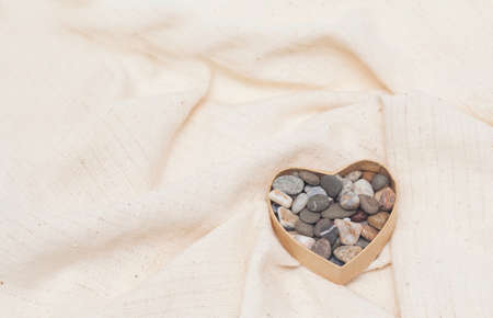 stone heart in cardboard box in the form of heart on linen fabric Stock Photo - 17174486