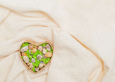 Colored  stone heart in cardboard box in the form of heart on linen fabric Stock Photo - 17174485