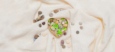 Colored  stone heart in cardboard box in the form of heart on linen fabric Stock Photo - 17174502