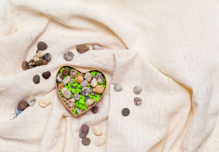 Colored  stone heart in cardboard box in the form of heart on linen fabric Stock Photo - 17174514