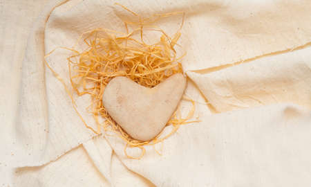 stone in the shape of a heart lies on linen fabric Stock Photo - 17174512