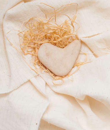 stone in the shape of a heart lies on linen fabric Stock Photo - 17174504