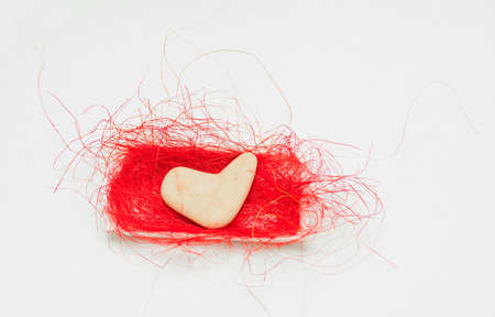 stone in the shape of a heart lies on a red sisal Stock Photo - 17174501