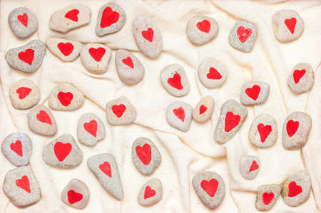 stones painted with red hearts on linen fabric Stock Photo - 17174497