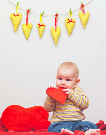 little sweet boy playing with heart on a red blanket Stock Photo