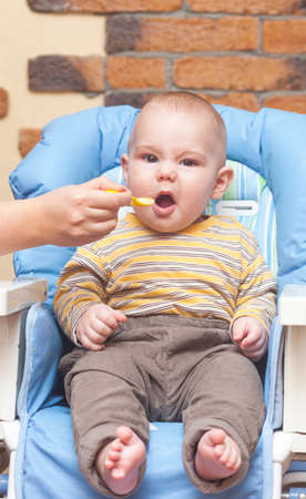Eating little boy is looking very angry and annoyed Stock Photo