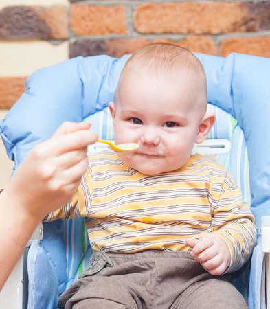 Baby is being fed by her mum sitting on   high chair Stock Photo - 17181977