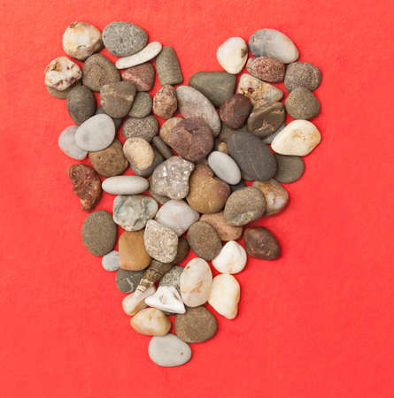 stones are in the form of heart on red paper photo
