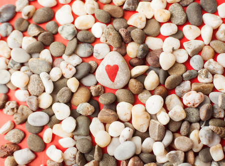 stones painted with red heart on red paper photo