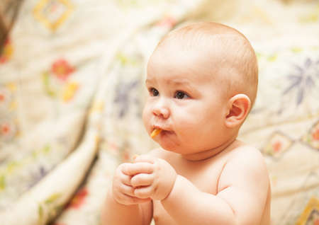 cute child learning to eat a biscuit