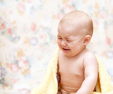 Baby crying in a yellow towel sitting  on the floor
