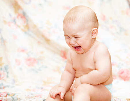 Baby crying sitting  on the floor Stock Photo