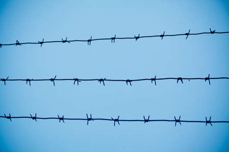 Barbed wire with fence on blue sky background Stock Photo - 17560954