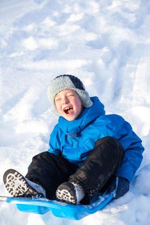 Un joven muestra su emoción trineo en invierno.