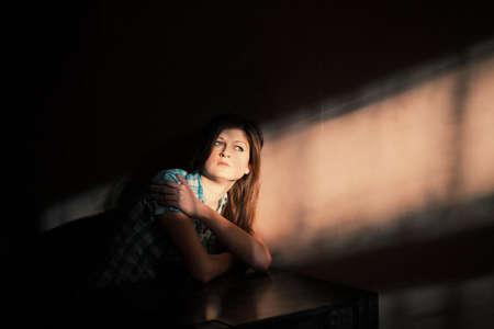 Mujer joven que sufre de una depresión severa en una línea de luz