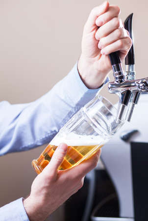 beer tap: glass being filled with draft beer by barman