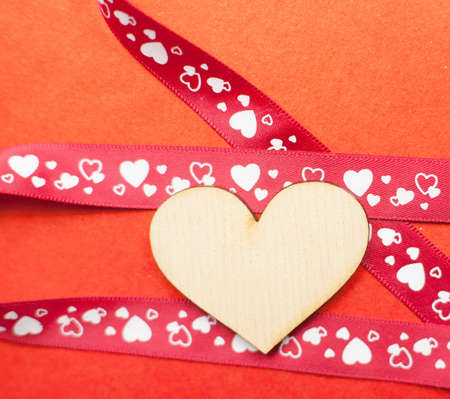 wood heart with gift ribbon on red paper