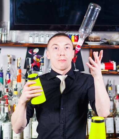 Young professional barman in action with shaker and bottle making cocktail drinks Stock Photo