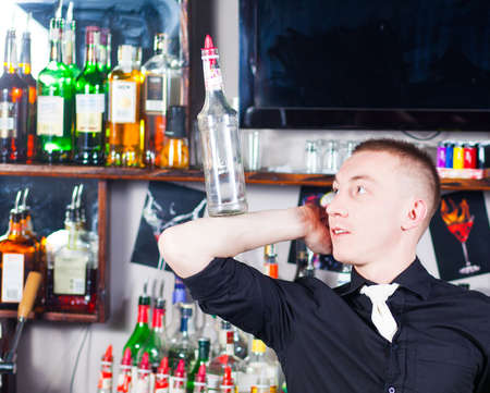 Young professional barman in action with bottle making cocktail drinks