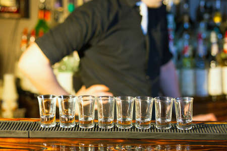 Young professional barman in action making  drink shots photo
