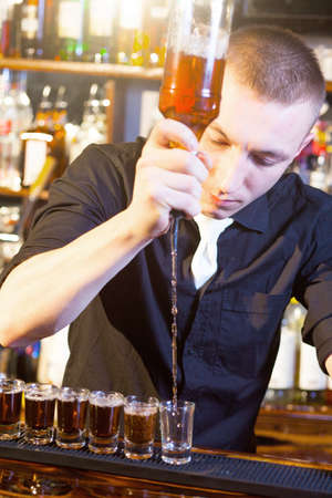 Young professional barman in action making  drink shots