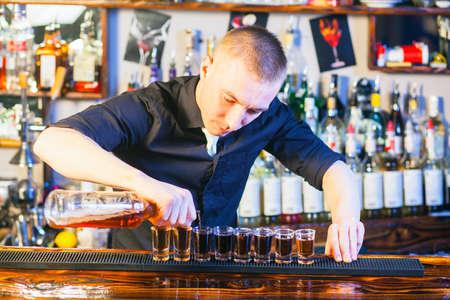 Joven barman profesional en acción haciendo disparos bebidas Foto de archivo